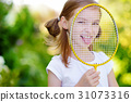 Cute little girl playing badminton outdoors 31073316
