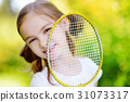 Cute little girl playing badminton outdoors 31073317