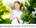 Cute little girl playing badminton outdoors 31073341