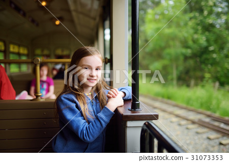Happy little girl riding a train in a theme park 31073353
