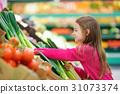 Little girl choosing fresh leek in a food store 31073374