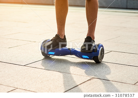 Legs of man on hoverboard. 31078537