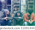 Group of men sit and talk outdoors in winter 31091444