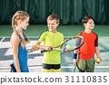 Happy children playing tennis on playground 31110835