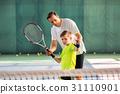 Skillful trainer teaching kid holding racquet 31110901