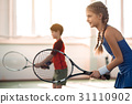 Excited children playing tennis on court 31110902