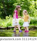 Two cute little sisters playing in river  31114124