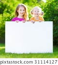 Two cute sisters holding big blank whiteboard 31114127