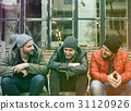 Group of men sit and talk outdoors in winter 31120926