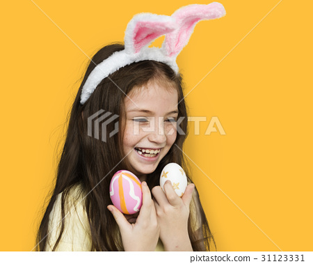 Kid with a bunny hairband holding eggs 31123331