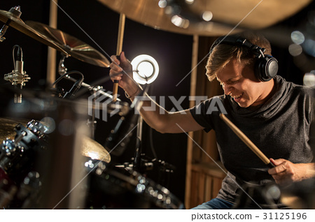 male musician playing drums and cymbals at concert 31125196