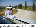 A tourist with a map at the car checks the route to the destinat 31135385