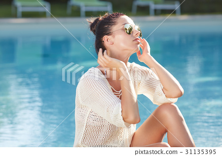 Beautiful young woman sitting by swimming-pool 31135395
