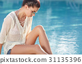 Beautiful young woman sitting by swimming-pool 31135396