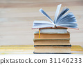 Open book, stack of hardback books on wooden table 31146233