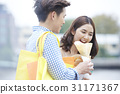 a man is holding crepe for his girlfriend eating. 31171367