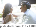 a man is touching his girlfriend hair with smiles on their faces. 31171389
