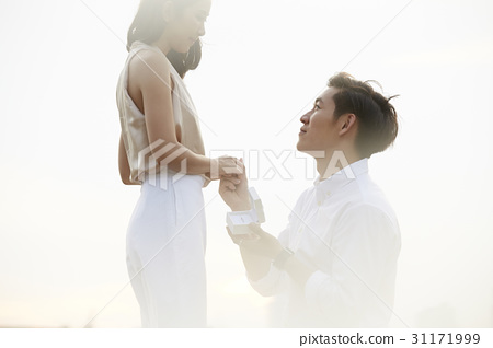 The man is holding hand and proposing the girl. 31171999