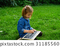 A girl drawing while on grass 31185560