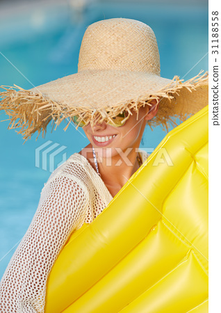 Young happy woman relaxing in a swimming pool 31188558