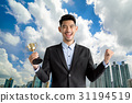 Handsome man in a suit with prize cup over a cityscape backgroun 31194519