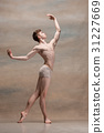 The male ballet dancer posing over gray background 31227669