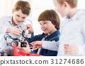 Cheerful children holding robot 31274686