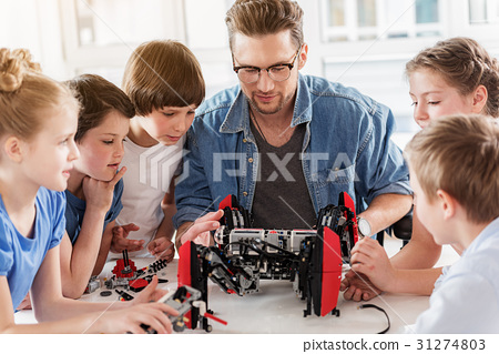 Curious technical team working with robot 31274803