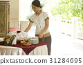 The staff is preparing the dinnerware set on the table. 31284695