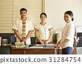 Female guest and receptionists are standing, smiling at the reception. 31284754