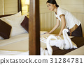 The beautiful maid is arranging the bed in hotel room. 31284781