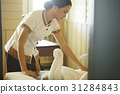 Housekeeper is cleaning a bed on a room 31284843