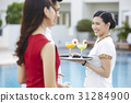 Resort waitress is smiling at the couple on a poolside 31284900