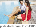 A couple is sitting, enjoying and smiling on a poolside 31284905