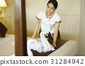 A housekeeper is preparing bed in hotel room. 31284942
