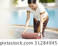A maid is putting a towel on bed near a pool. 31284945