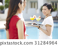 A waitress is carrying a tray with cocktails and greeting guests. 31284964