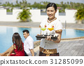 A photo of a waitress bringing drinks for guests at a pool. 31285099