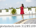 A photo of a girl standing and posing beside a pool. 31285109