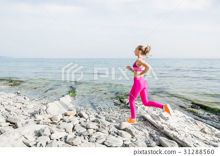 Young attractive fitness girl running on beach 31288560