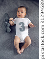 newborn to three months lying on the bed with the 31294689