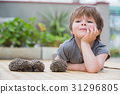 Little boy playing with hedgehog 31296805