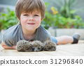 Little boy playing with hedgehog 31296840
