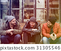 Group of men sit and talk outdoors in winter 31305546