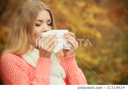 Sick ill woman in autumn park sneezing in tissue. 31319924