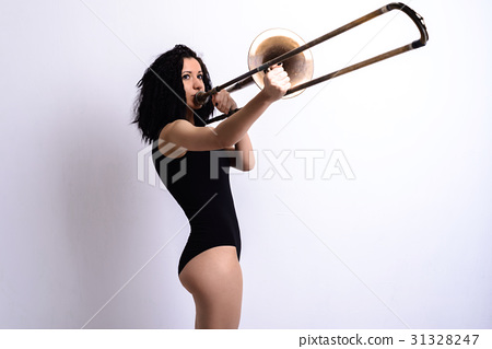 Slender young brunette girl playing the trombone 31328247