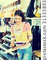 Teenage girl shopping drum kit in music studio 31333893