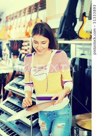 Teenage girl shopping drum kit in music studio 31333893