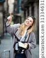 Blond cheerful girl holding brochure in hands 31334631