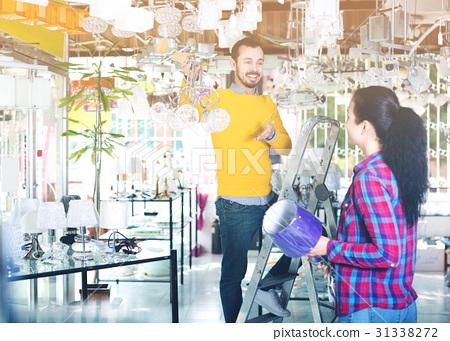 Man and girl choosing modern chandelier 31338272